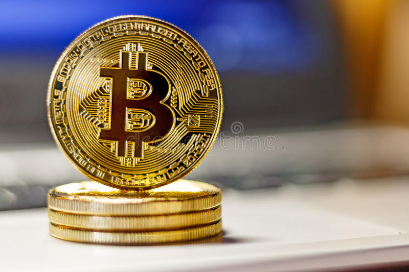 Golden bitcoins on the laptop touchpad closeup. Cryptocurrency virtual money royalty free stock images