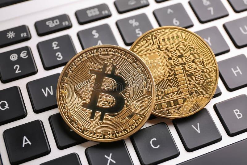 Golden bitcoins on PC keyboard stock photos