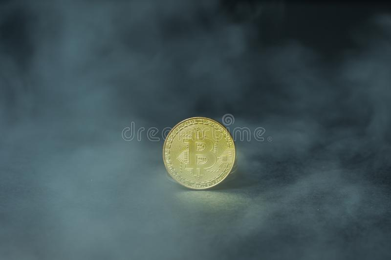 Golden bitcoins with smoke on black background. Business concept. Internet security and protection concept. stock image