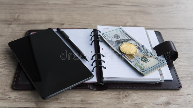 Golden bitcoins on a us dollar, notebook, tablet and pen. Bitcoin crypto currebcy on US dollars. Digital currency royalty free stock images