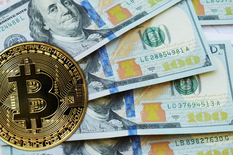 Golden Bitcoins on US dollars. Digital currency close-up. Crypto currency top view. Real coins of bitcoin on banknotes of one stock photos