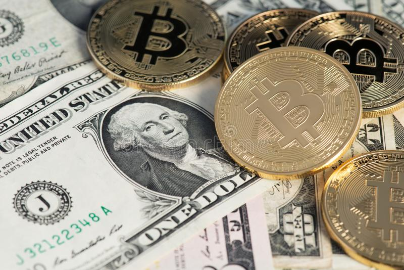 Golden Bitcoins on US dolllars close up image. Bitcoin virtual money and banknotes of dollars. stock image