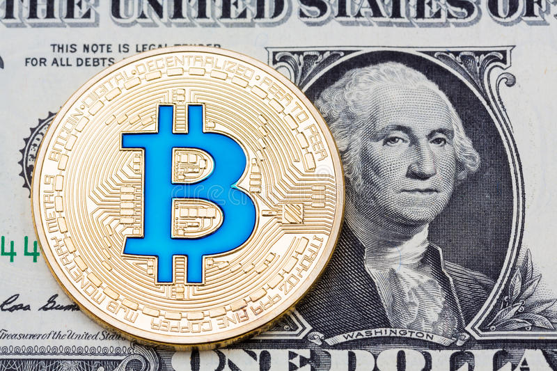Golden blue bitcoin coin on us dollars close up. stock images