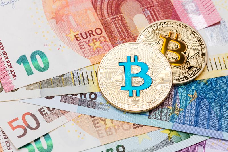Golden blue and yellow Bitcoins close-up on euro currency backgr stock photo