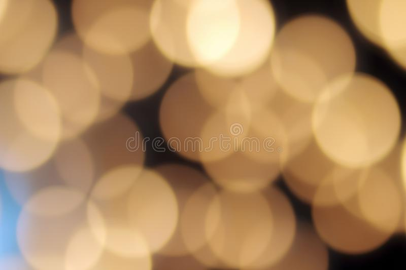 Golden bokeh on a black background, abstract dark backdrop with defocused warm lights and blue highlight royalty free stock photos