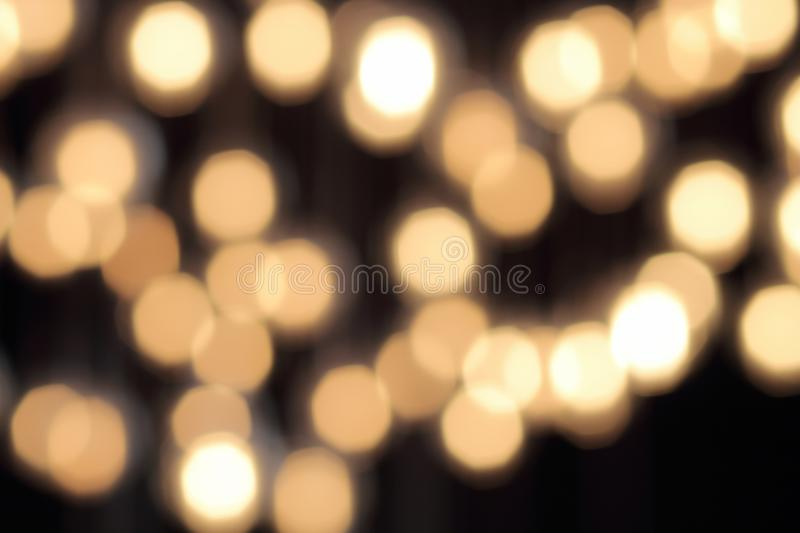 Golden bokeh on a black background, abstract dark backdrop with defocused warm lights.  stock images