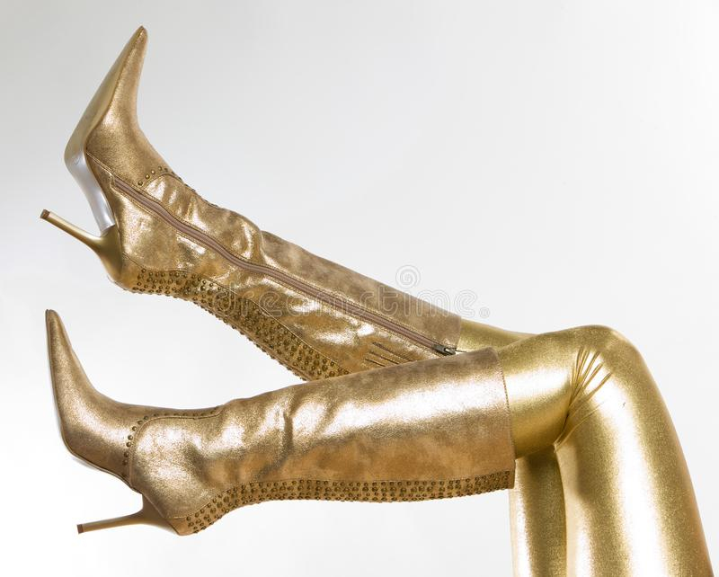 Golden boots. Inside, indoor, indoors, interior, interiors, person, persons, people, woman, women, female, adult, adults, one, alone, single, footgear royalty free stock photos