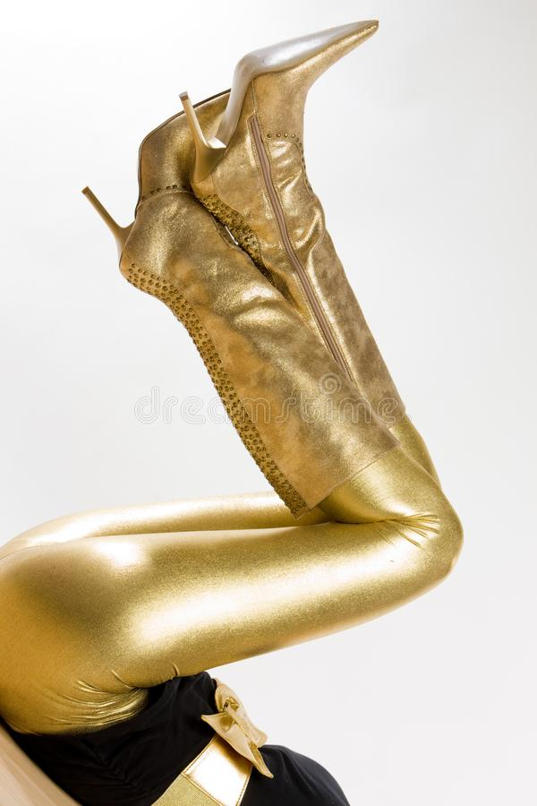 Golden boots. Inside, indoor, indoors, interior, interiors, person, persons, people, woman, women, female, adult, adults, one, alone, single, footgear stock photo