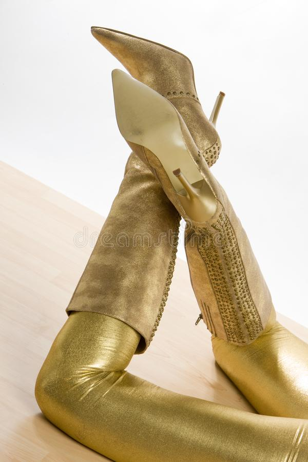 Golden boots. Inside, indoor, indoors, interior, interiors, person, persons, people, woman, women, female, adult, adults, one, alone, single, lying, lie, down royalty free stock images
