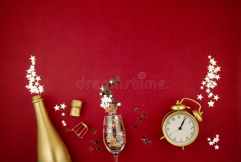 Golden bottle of champagne, glass, alarm clock and confettie over the red background. Party, new year, christmas celebration. Top view Golden bottle of champagne stock photo