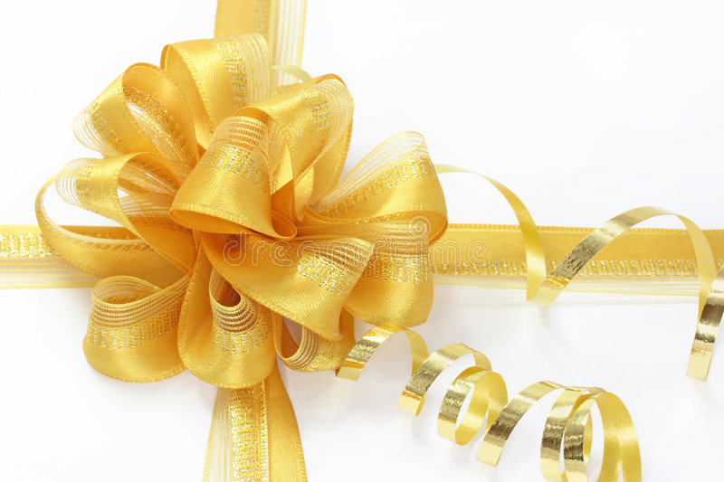Golden bow with a curly ribbon royalty free stock photography