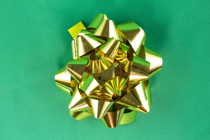 Golden bow on green background.  royalty free stock image