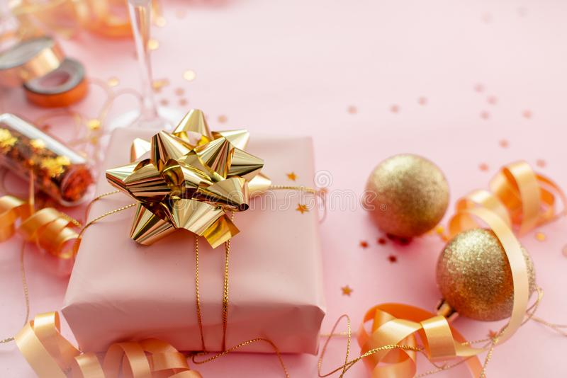Gift box with golden bow on pink coral background with stars and sparkles. Festive concept copyspace top horizontal view. 2020 New Year concept copyspace top stock photography