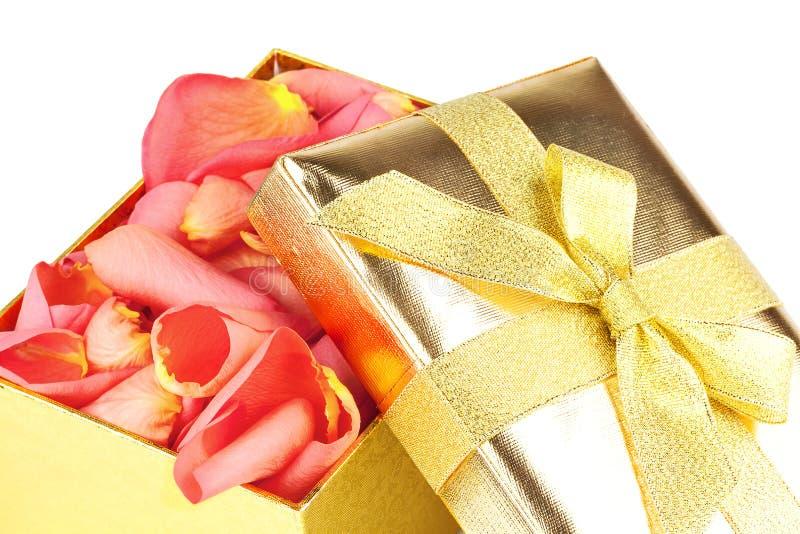 Golden box full of roses petals stock photography