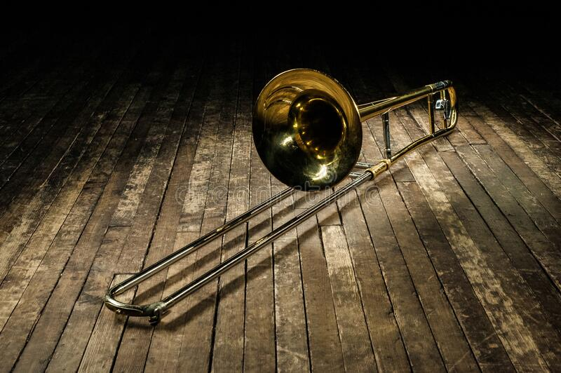 Golden brass instrument trombone lies on a brown wooden stage stock photos