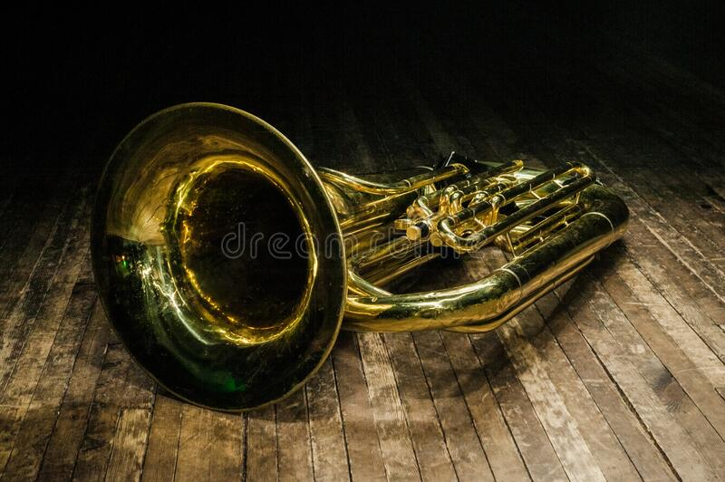Golden brass instrument tuba lies on a brown wooden stage in the light of the spotlight stock photography