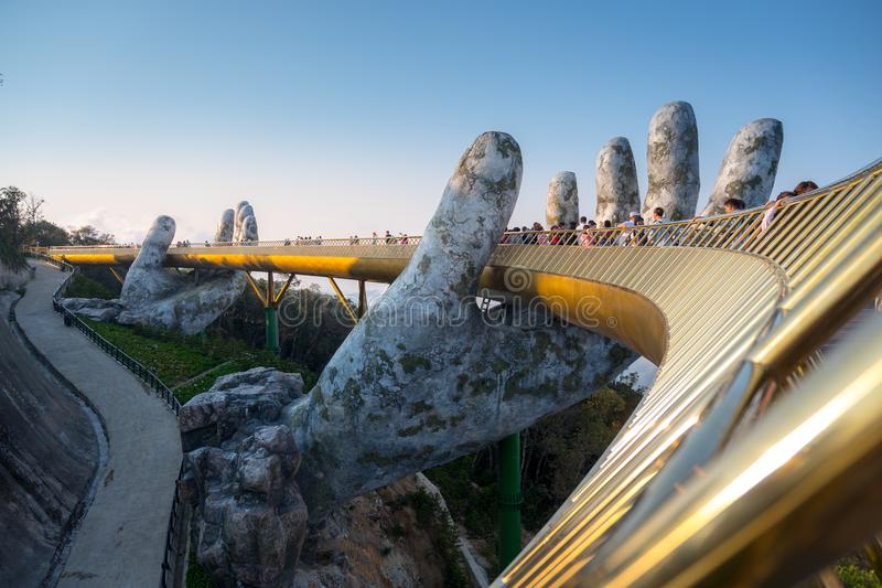 The Golden Bridge is lifted by two giant hands in the tourist resort on Ba Na Hill in Danang, Vietnam. stock photography