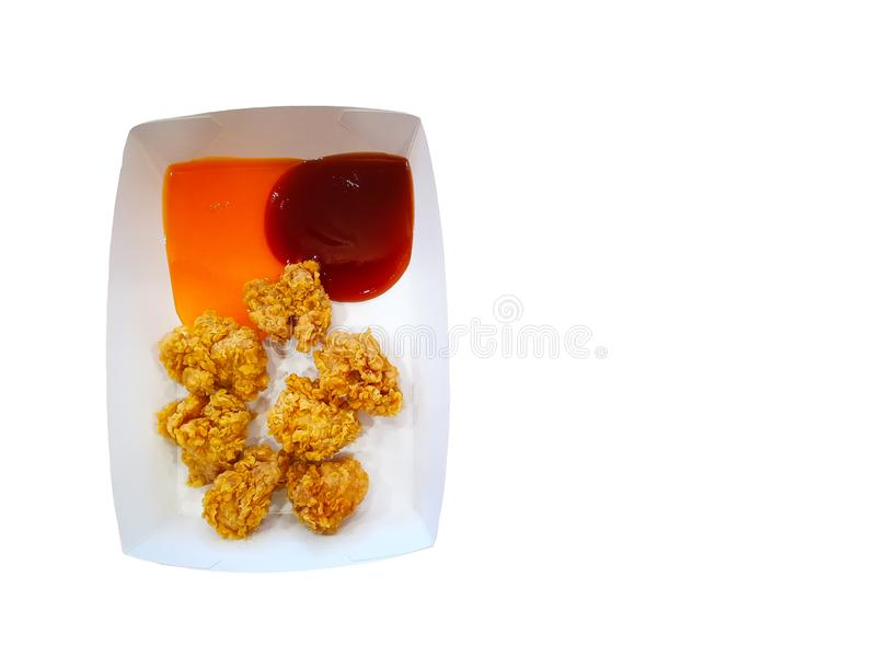 Golden brown fried chicken in small pieces on square white paper plate with Tomato ketchup and chili sauce isolated on white backg stock image