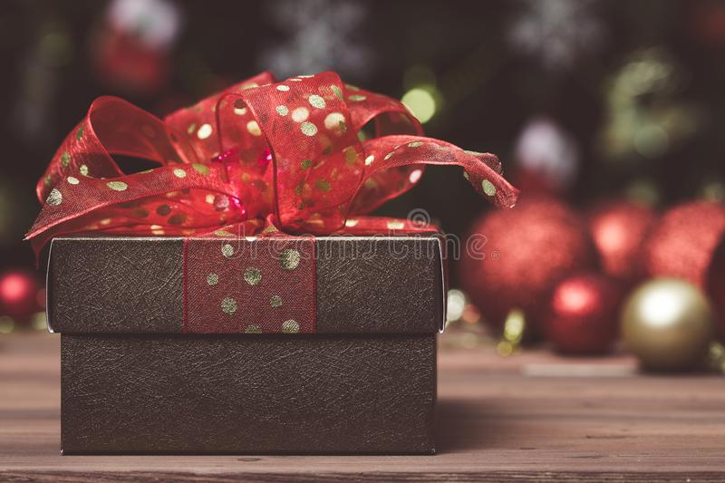 A golden brown gift box with red ribbon close up, blurred background of Christmas ornaments stock photo