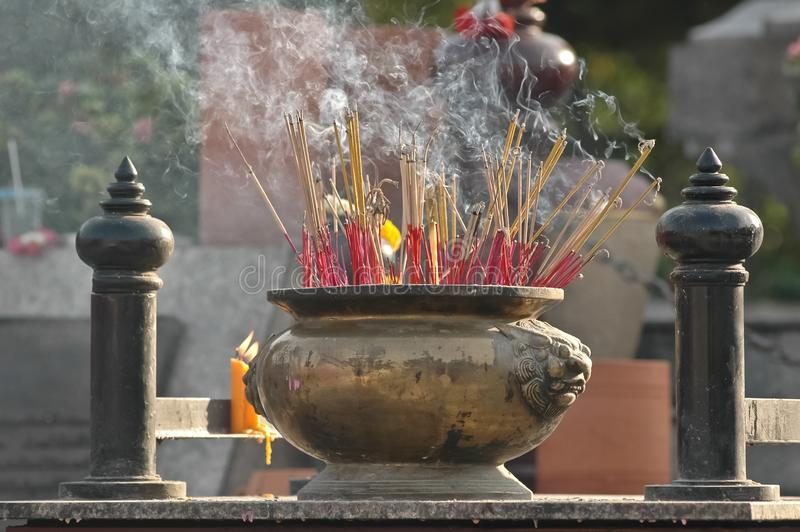 Golden bucket of fragrance sticks in Chinese temple stock image