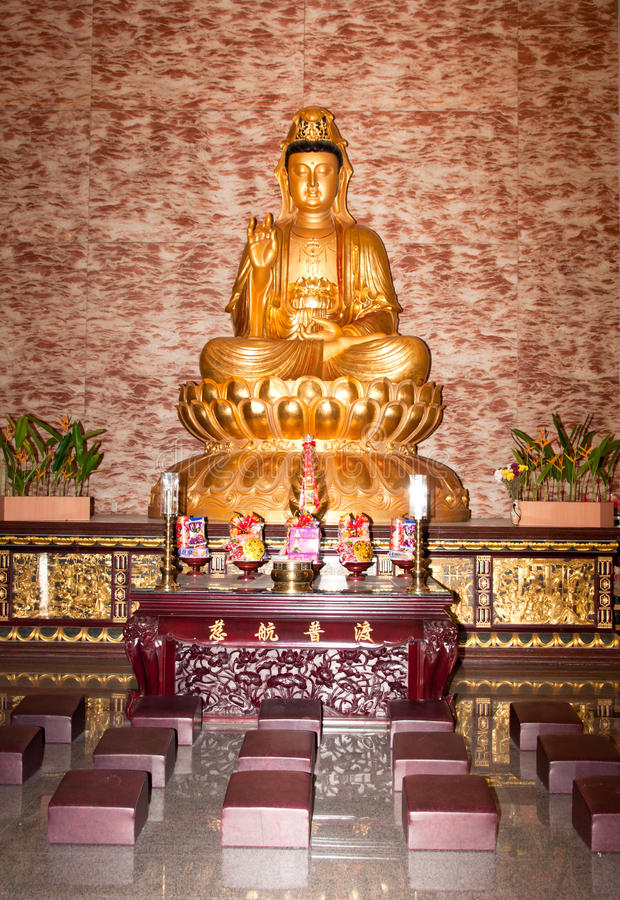Golden Buddha Altar. A portrait of golden Buddha inside the Buddhist temple with decorated offering on the altar stock image
