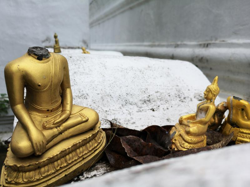 Golden Buddha figurines with missing head, detail and closeup of gold Buddha statues royalty free stock photos