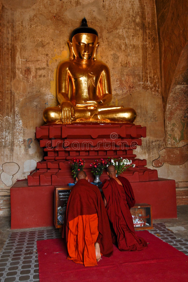 Golden buddha with monks praying royalty free stock photo