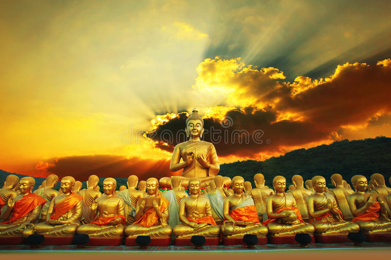 golden buddha statue in buddhism temple thailand against dramatic sun rising with ray beam background stock photography