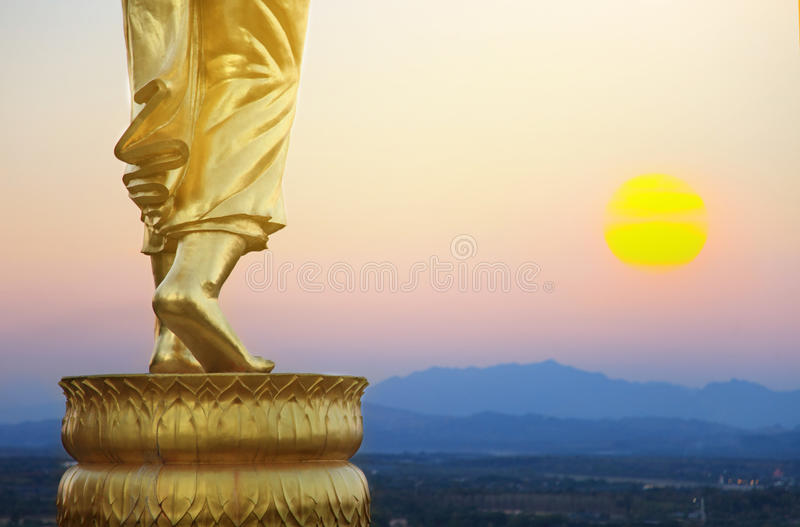 Golden buddha statue in Khao Noi temple Nan Province Thailand. Sunrise nature and golden buddha statue in Khao Noi temple Nan Province Thailand royalty free stock image