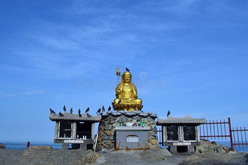 The golden Buddha statue, surrounded by birds. Pic was taken close to Haedong Yonggungsa in August 2017. royalty free stock photo