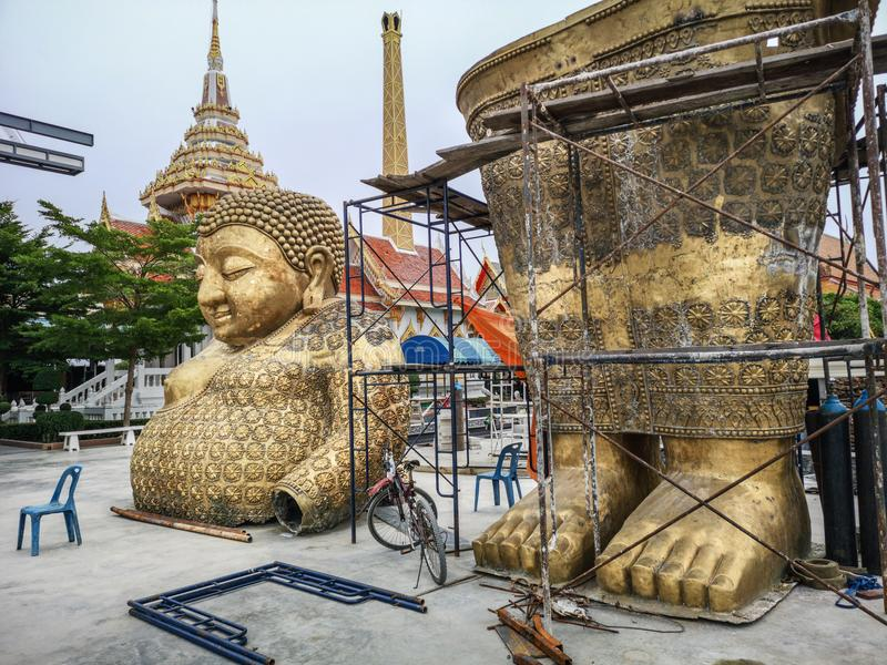 Golden Buddha statue in two parts ready to be assembled in buddhist temple yard in Thailand royalty free stock image