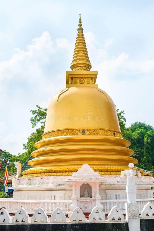 Golden buddhist dagoda or stupa monument. With Buddha statue on a niche on the front of Dambulla cave temple on Sri Lanka island stock photo