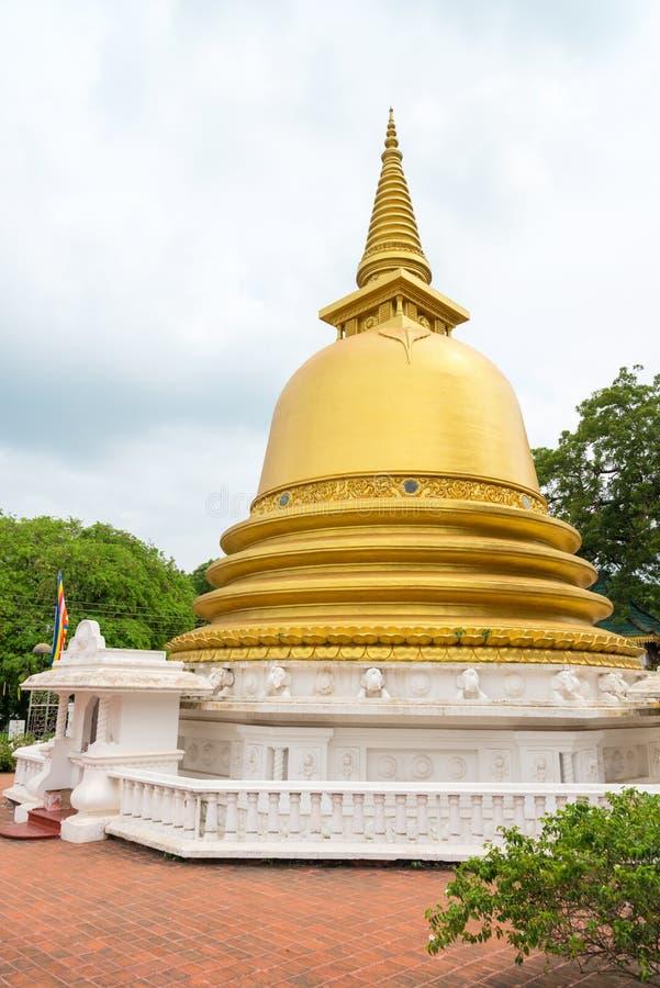 Golden buddhist dagoda or stupa monument. With white fence around on the front of Dambulla cave temple on Sri Lanka island stock photo