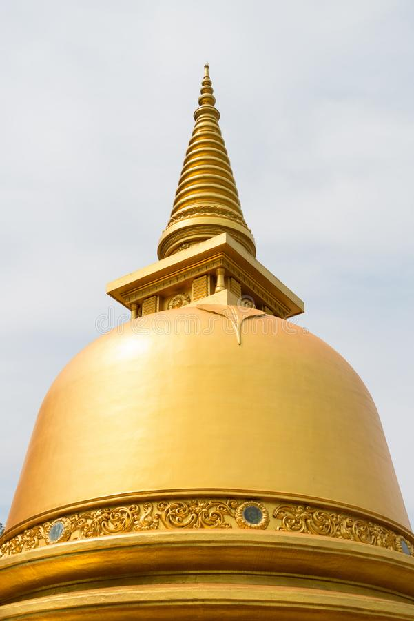Golden buddhist dagoda or stupa monument. Top with cloudy sky on background royalty free stock image