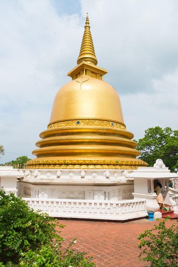 Golden buddhist dagoda or stupa monument. With white fence on the front of Dambulla cave temple on Sri Lanka island stock photo