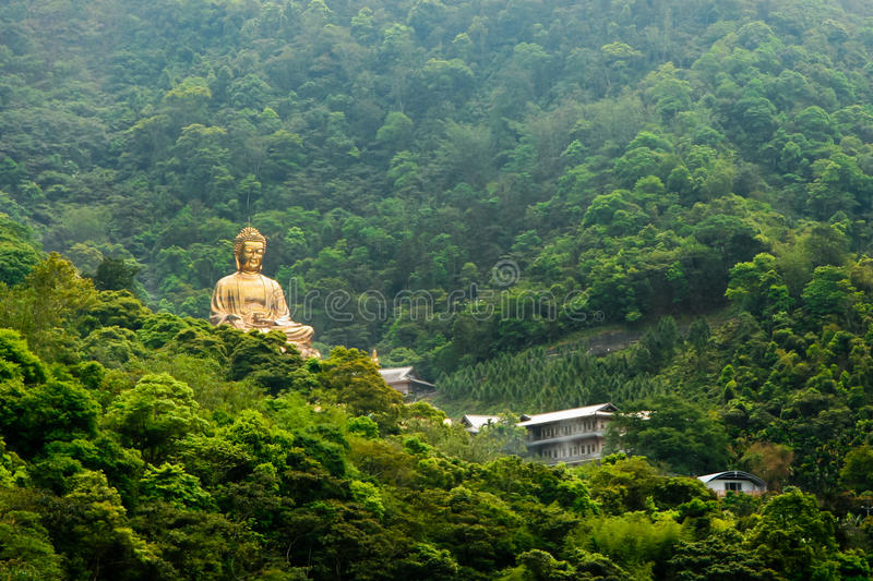 Golden Budha. Fushing Village, Taiwan, March 30, 2010. A golden Budha statue overlooking the village. Shot from Christian Renai Nursing Home royalty free stock photography