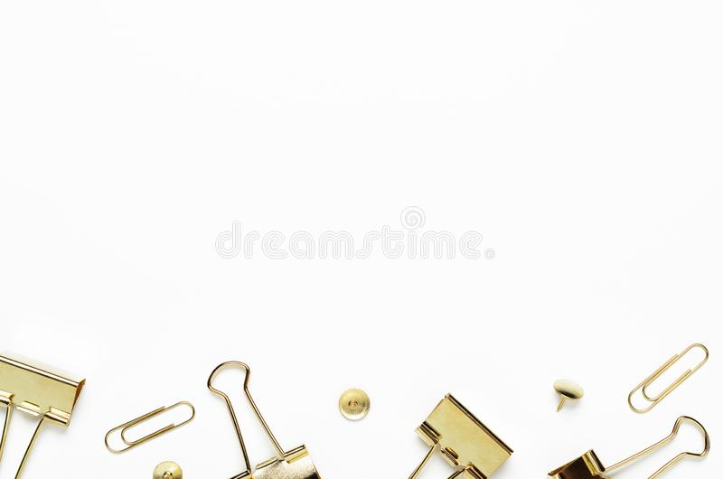 Golden buttons, paper clips and stationery clips on a white background. Frame of office stationery. Copy space, top view. Flat lay stock image