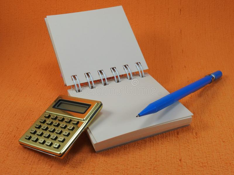 A golden calculator, a small blank notepad and a blue mechanical pencil. royalty free stock images