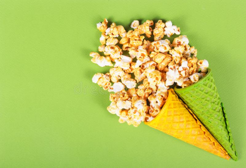 Golden caramel popcorn in wafer cone. Summer sweets. Two waffle cones and scattered popcorn. Sweet air corn. Copy space stock photos