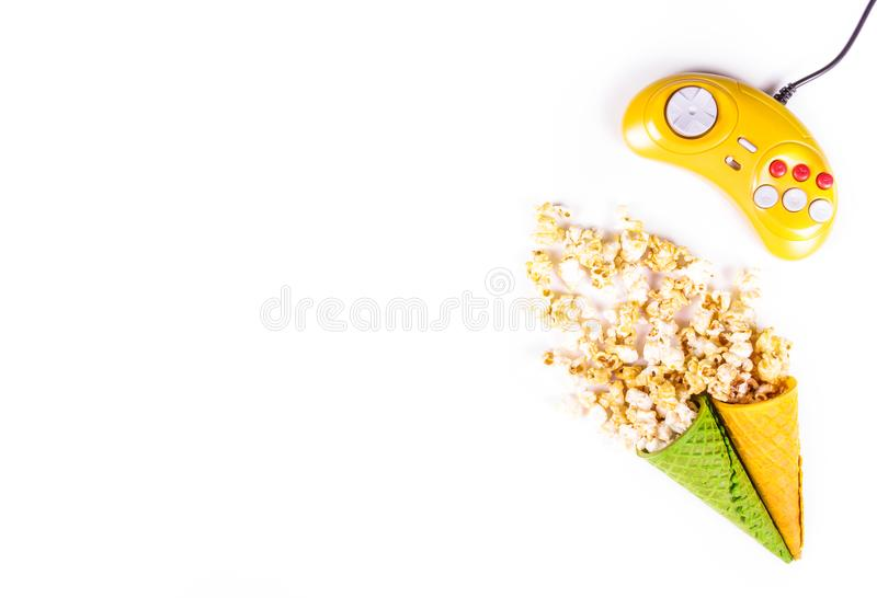 Golden caramelized popcorn scattered on white background. Video game console GamePad. Yellow retro joystick. royalty free stock photos
