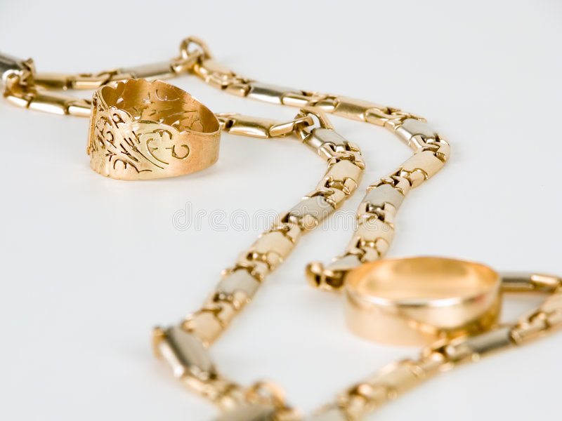 A golden chain and two rings royalty free stock image