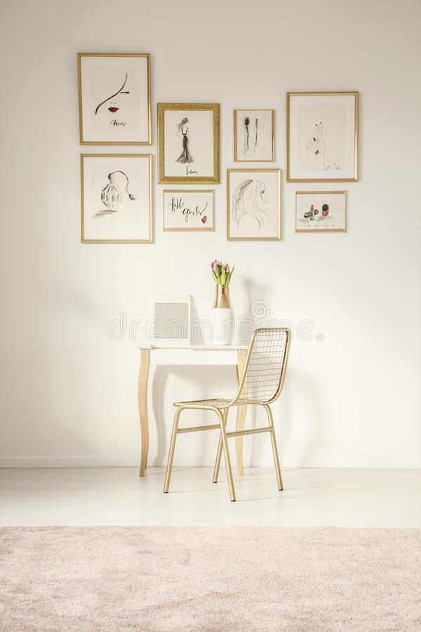 Golden chair by an elegant vanity table with a mirror. By a white wall with drawings gallery in a feminine bedroom royalty free stock image