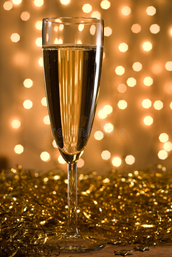 Golden champagne. Champagne flute among golden ribbons, defocused lights background - shallow DOF, selective focus on the glass stock photos