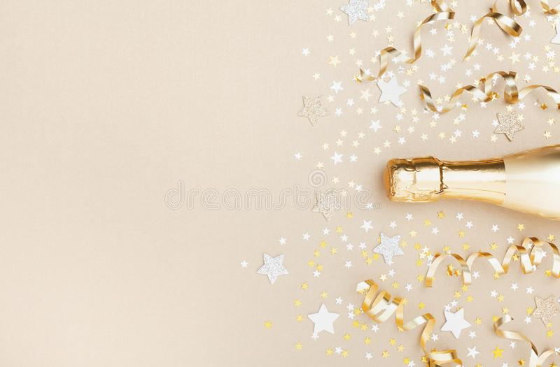 Golden champagne bottle with confetti stars and party streamers top view. Christmas, birthday or wedding background. Flat lay. Style royalty free stock image