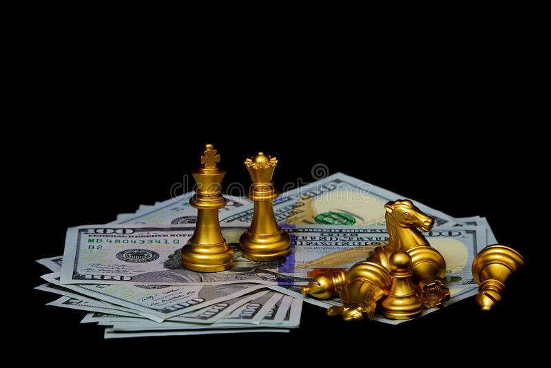 Golden chess pieces on american dollars against dark background. American dollars with golden chess pieces still life background royalty free stock photos