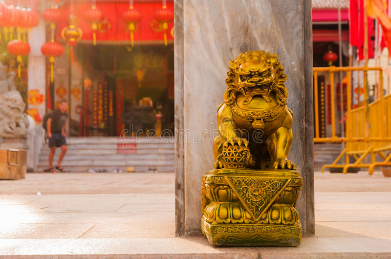 Golden chinese lion guardian sculpture in front of the gates to royalty free stock photography