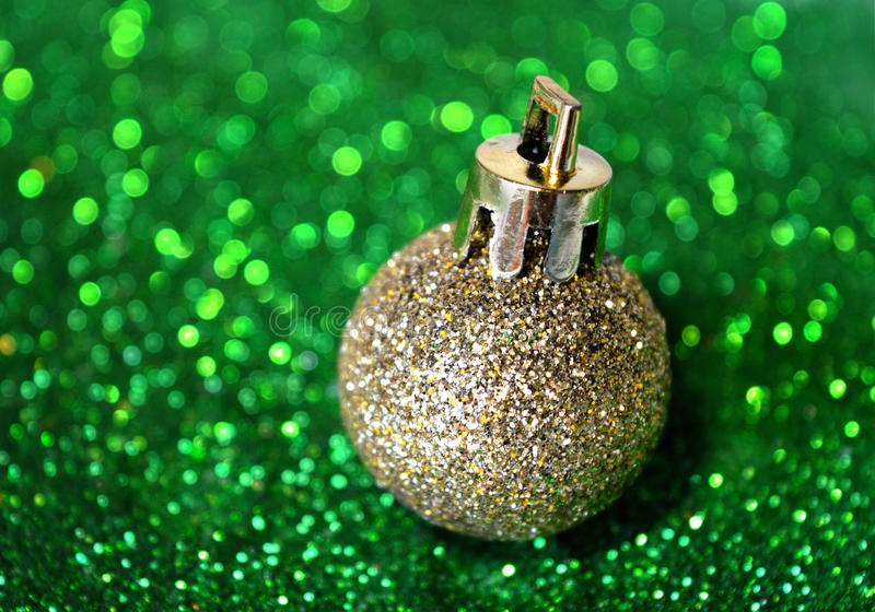 Golden Christmas ball on blurry background of green glitter. Golden Christmas ball on the blurry background of green glitter stock photos