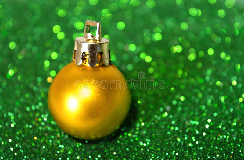 Golden Christmas ball on blurry background of green glitter. Golden Christmas ball on the blurry background of green glitter royalty free stock images