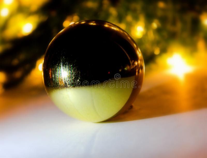 Golden christmas ball .  Christmas tree and lights. Golden christmas ball .  Festive decoration on bokeh background.. Christmas tree and lights stock photos