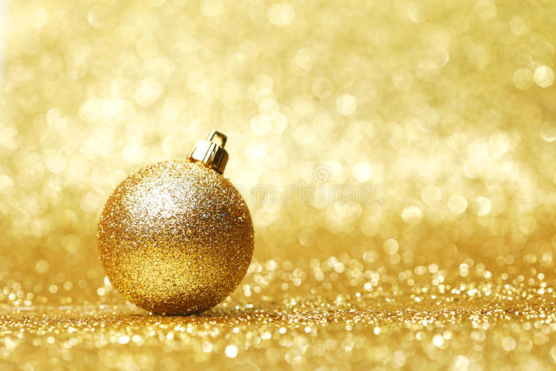 Golden christmas ball. On glitter background close-up stock photos